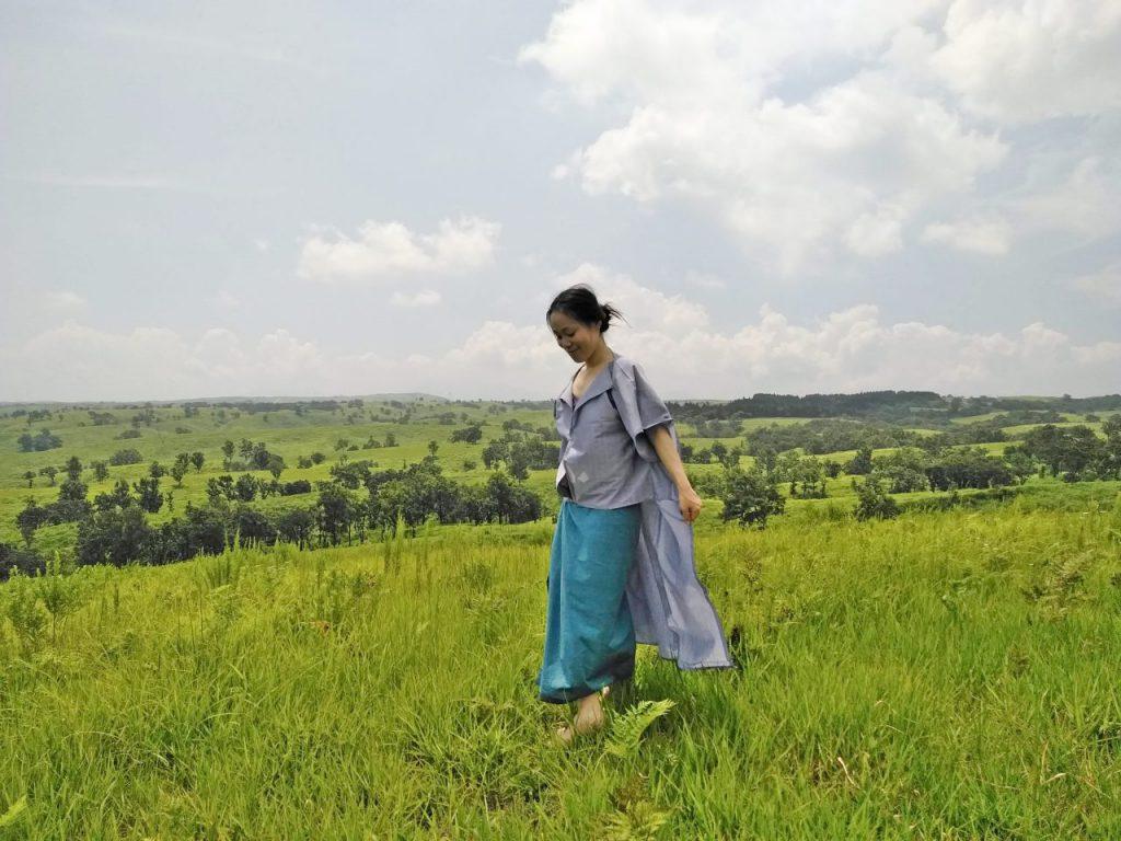 TAKSU AMANATのお洋服を着て丘を歩く女性