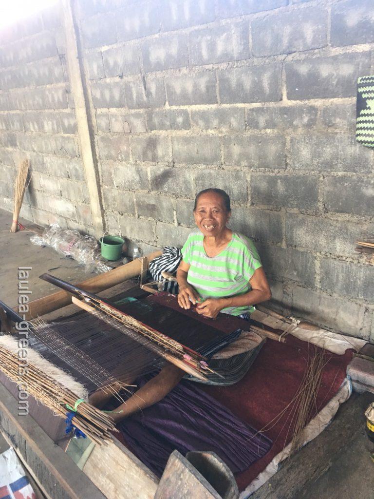 腰機で布を織るおばあちゃん
