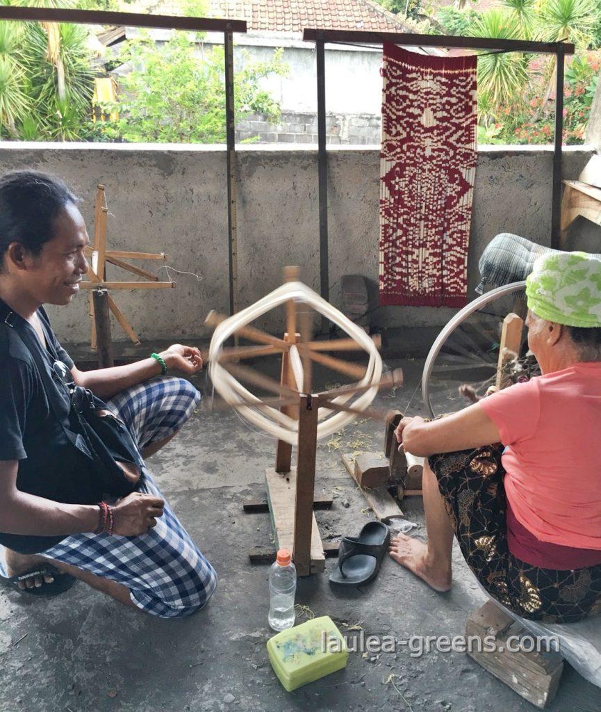 糸を紡ぐ工程を見守る男性