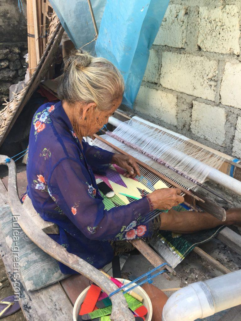 腰機をで布を織るおばあちゃん